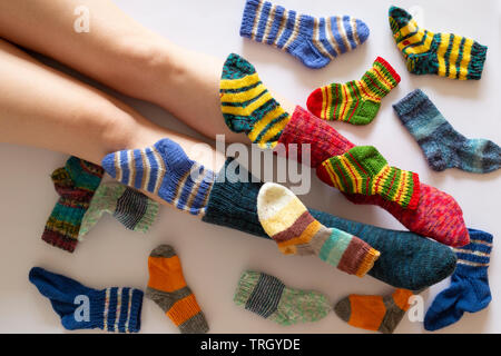Top view of an assortment of colorful woolen socks of various sizes on white background with a pair of feet wearing a red and a blue sock - Stock Photo