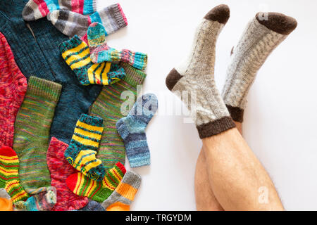 Top view of an assortment of colorful woolen socks of various sizes on white background with a pair of feet wearing gray brown socks - Stock Photo