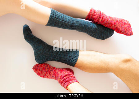 Top view of two pairs of legs wearing a red and a blue sock on white background - Stock Photo