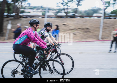 San Francisco, USA. 2nd June, 2019. Two cyclists leaving the Cow Palace at the start of the AIDS/Lifecycle, the 7 day 545-mile ride from SF to LA - Stock Photo