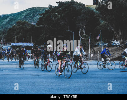 San Francisco, USA. 2nd June, 2019. Cyclists leave the Cow Palace at the start of the AIDS/Lifecycle just as the sun first reaches the hilltops above. - Stock Photo