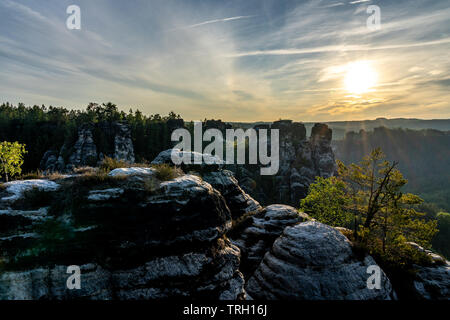 view on sandstone rocks and mountains at sunrise from trail to bastion bridge in saxon switzerland, germany - Stock Photo