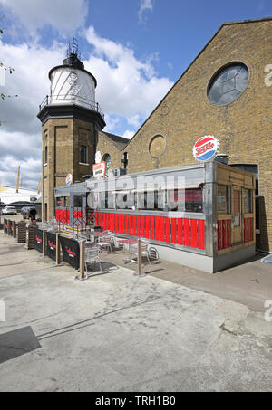 Fat Boys Diner, the American-style café at Trinity Buoy Wharf next to the river Thames in London, UK Show Trinity House lighthouse beyond. - Stock Photo