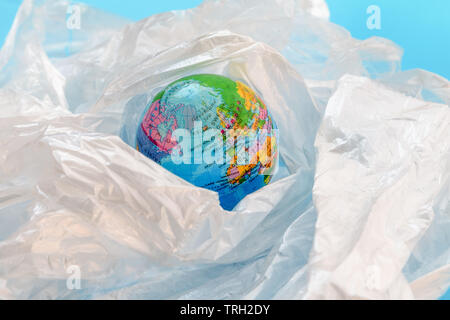 Concept of the plastic pollution problem in the world.  The planet earth is floating around in a soup of white plastic bags on against blue background - Stock Photo