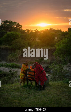 Masai Mara, Kenya, Africa – August 10, 2018: A group of Masai men in traditional clothes resting at dawn after a long night protecting tourist from da - Stock Photo
