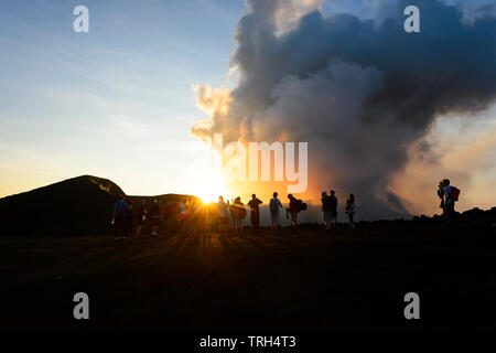 Tourists walking on the crater rim of smoking Mt Yasur Volcano at sunset, Tanna Island, Vanuatu - Stock Photo