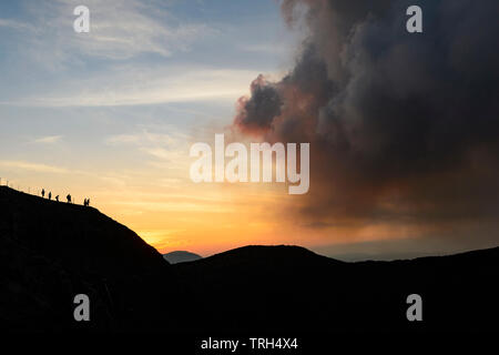 Silhouettes of tourists walking along the crater rim path, Mt Yasur Volcano at sunset, Tanna Island, Vanuatu - Stock Photo