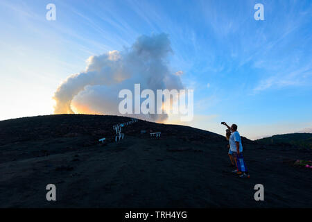 Tourists standing on the slopes of erupting Mt Yasur Volcano at sunset, Tanna Island, Vanuatu - Stock Photo