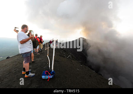Tourists standing on the rim of erupting Mt Yasur Volcano at sunset, Tanna Island, Vanuatu - Stock Photo