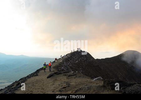 Tourists walking on the crater rim of Mt Yasur Volcano at sunset, Tanna Island, Vanuatu - Stock Photo