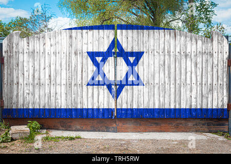 Close-up of the national flag of Israel on a wooden gate at the entrance to the closed territory on a summer day. The concept of storage of goods, ent - Stock Photo