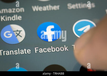 Facebook logo icon on mobile phone screen - Stock Photo