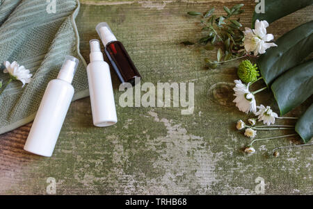 Cosmetic's container, jars and flowers on green wooden background, top view. Towel, monstera and cosmetic's bottles on old vintage table. - Stock Photo