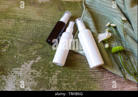 Cosmetic's container, jars and flowers on green wooden background, top view. Towel and cosmetic's bottles on old vintage table. - Stock Photo