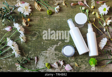 Cosmetic's container, jars and flowers on green wooden background, top view. White dispensers and bottles with wild flowers on old vintage table. - Stock Photo