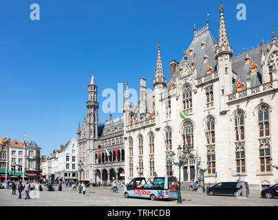 Tourists wandering around the historic market place going past the Provincial Court Provinciaal Hof in the Markt central Bruges Belgium EU Europe - Stock Photo