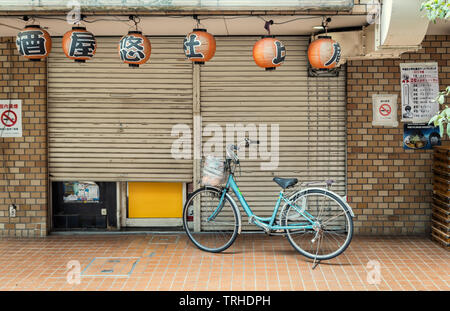 A single bicycle outside a closed shop in Tokyo, Japan.  Japanese lanterns hang at the front of the shop - Stock Photo