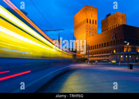 Oslo city centre, view at night of a city tram speeding towards the Town Hall building (Radhus) in the central harbour district of Oslo, Norway. - Stock Photo