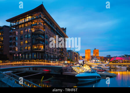 Oslo harbour, view at night of the harbour district (Aker Brygge) in central Oslo with the Town Hall building (Radhus) in the distance, Norway. - Stock Photo