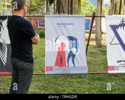 A European tourist looks at a poster declaring 'Human rights are only for whites' at the Museum Garden of Anti Arrogance, housed in the former America - Stock Photo