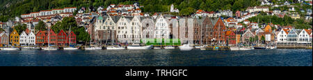 North Sea, behind a colorful wooden houses front with attached sailboats in the harbor of Bryggen, behind it further houses of the place above hotel c - Stock Photo