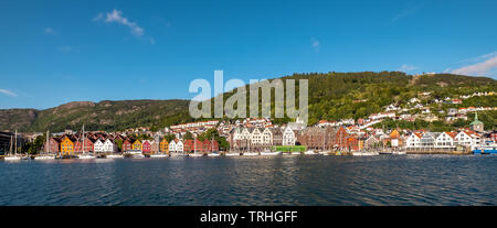 North Sea, behind a colorful wooden houses front with attached sailboats in the harbor of Bryggen, behind it more houses of the place above hotel comp - Stock Photo