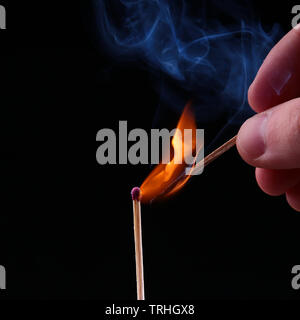 Ignition of a match, with smoke on dark background. Hand holding burning match stick - Stock Photo
