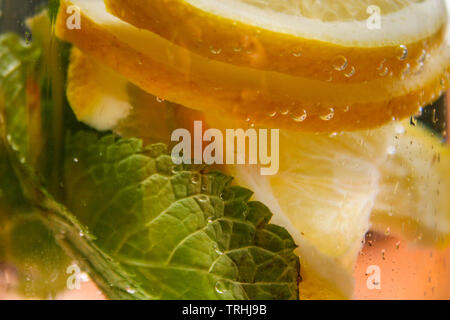 Glass bottle with fresh water, lemon and mint leaves - Stock Photo