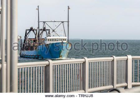 New Bedford, Massachusetts, USA - June 4, 2019: Commercial fishing vessel E.S.S. Pride framed by railings on hurricane barrier as she returns to New B - Stock Photo