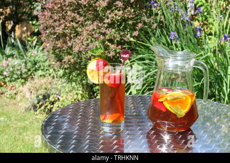 Jug of Pimms and Lemonade outside in sunshine with full glass - Stock Photo