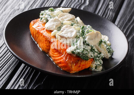 Italian salmon fillet recipe consists of topped with creamy spinach and mushrooms on a plate on the table. horizontal - Stock Photo
