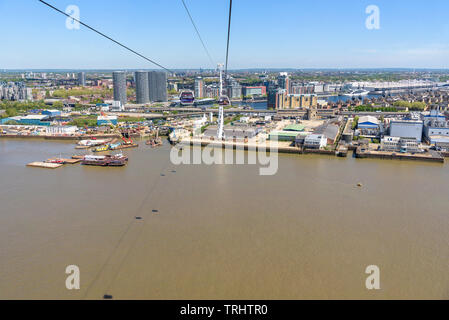 London, UK - May 1, 2018: Gondolas of Emirates Air Line go over River Thames in eastern London - Stock Photo