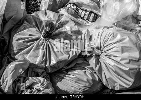 Skip full of rubbish bags - Stock Photo
