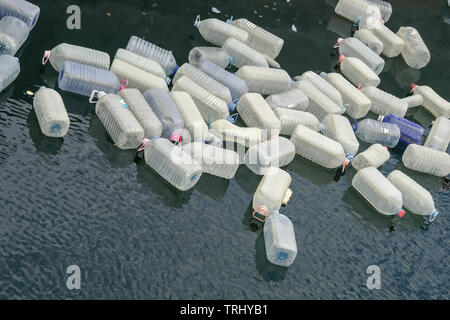 Empty large plastic containers, water cans floating in a bay in the Atlantic, waste, garbage disposal in the ocean, environmental pollution and plasti - Stock Photo
