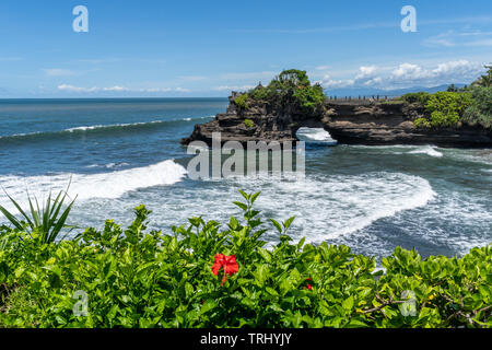 Tidal waves breaking on the coast of Hindu Tanah Lot Temple complex on Bali island, Indonesia - Stock Photo