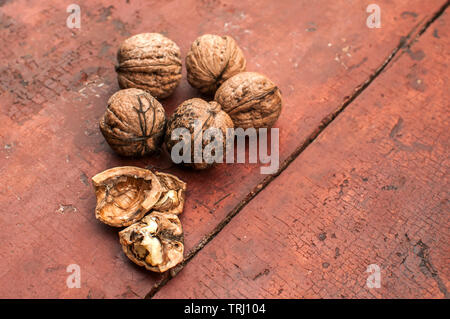 Whole and cracked walnut shells and cores closeup on old wooden boards surface as background - Stock Photo