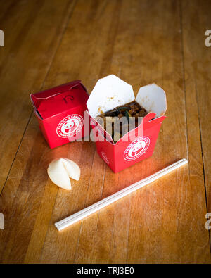 Takeout boxes of kung pao chicken from Panda Express restaurant, a fortune cookie, and chopstocks. - Stock Photo