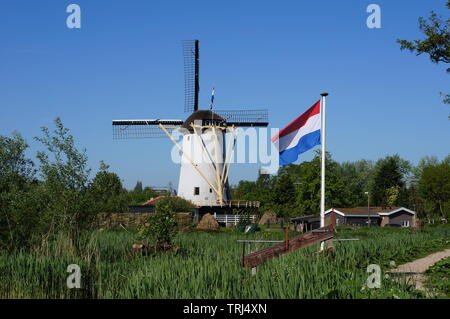 Typical Dutch windmill in the village of Schiedam in the Netherlands with the official Dutch flag. - Stock Photo