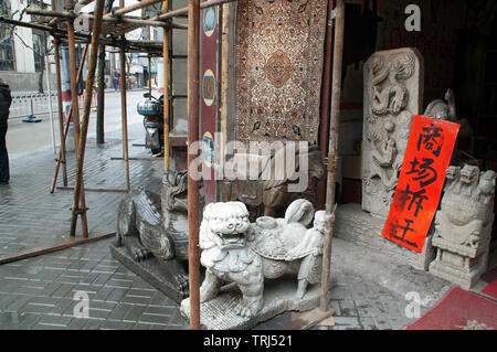 Shanghai China, stone carvings for sale on footpath in front of shop among scaffolding - Stock Photo