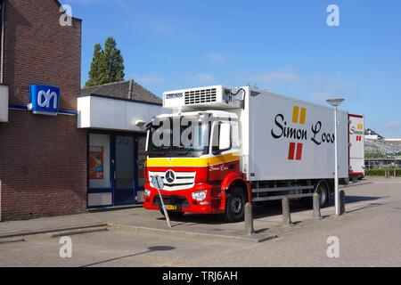 Simon Loos delivery truck near an Albert Heijn grocery store. - Stock Photo