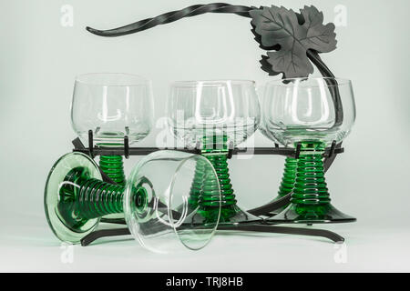 Five green wine glasses with rippled green stems sitting in a wrought iron rack with one glass tipped over. - Stock Photo