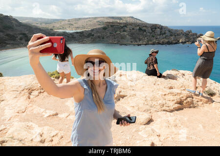 Tourists queuing for the photo, Golden Bay, Malta - Stock Photo