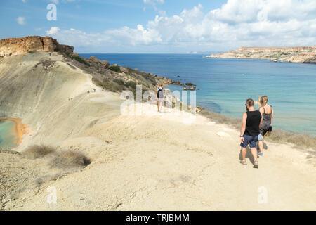 Tourists walking by Għajn Tuffieħa Bay,Malta - Stock Photo