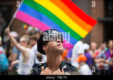 NEW YORK CITY - JUNE 25, 2017: A young NYPD police officer provides security on the sidelines of the annual Gay Pride Parade in Greenwich Village. - Stock Photo