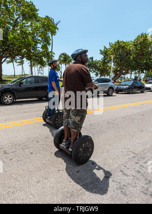 Miami, FL, USA - April 19, 2019: Tourists on segways on the Ocean Drive street in the historical Art Deco District of Miami South Beach in Miami, Flor - Stock Photo