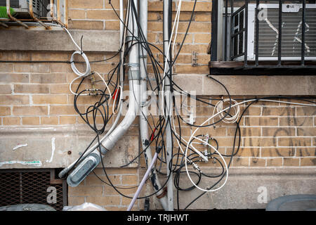 A rat's nest of wires and cables for telephone, internet and other utilities on the exterior of an apartment building in Brooklyn in New York on Saturday, June 1, 2019.  (© Richard B. Levine) - Stock Photo