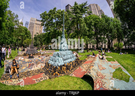 """Visitors to Madison Square Park enjoy the warm weather by lounging on the sculpture """"City in the Grass"""" by the artist Leonardo Drew on a warm Tuesday, June 4, 2019. The monumental public art commission presents a stylized cityscape over 100 feet long and provides an experiential activity, relaxing and lounging. The work will be on view and available for seating until December 15, 2019. (© Richard B. Levine) - Stock Photo"""