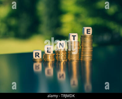 Symbol for a pension increase. Dice form the German word 'Rente' ('pension' in English) on increasing high stacks of coins. - Stock Photo