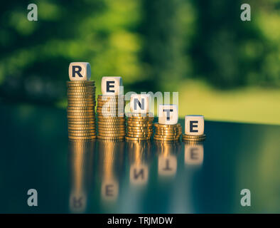 Symbol for a small pension. Dice form the German word 'Rente' ('pension' in English) on decreasing high stacks of coins. - Stock Photo