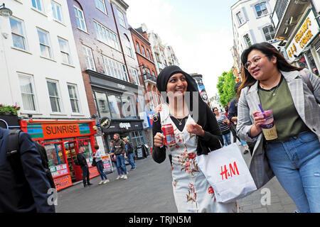 Young women walking on Gerrard Street in Chinatown London W1 England UK   KATHY DEWITT - Stock Photo